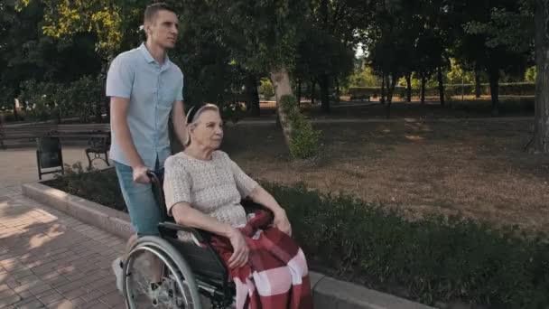 Mann geht mit alter Frau im Rollstuhl