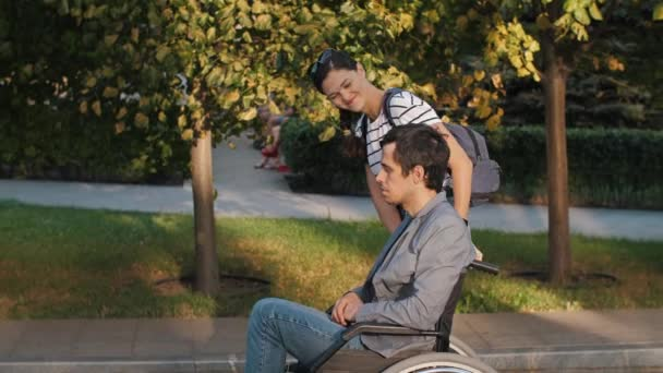 Frau unterstützt Mann im Rollstuhl