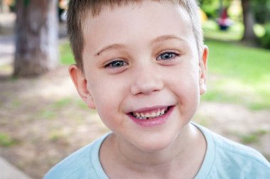 Funny adorable Caucasian 7 year old elementary school age child mildly smiling to the camera.