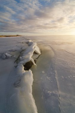 Ice and snow broken formation on frozen coast at sea in cold winter evening sunset sky clouds light.