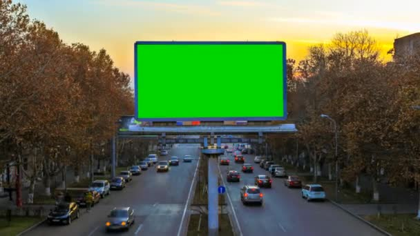 A billboard with green chroma key on the background of fast moving cars at sunset. The camera moves away.