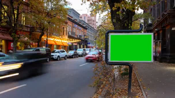 A billboard with a green screen on a background of autumn city traffic with long exposure. Time Lapse