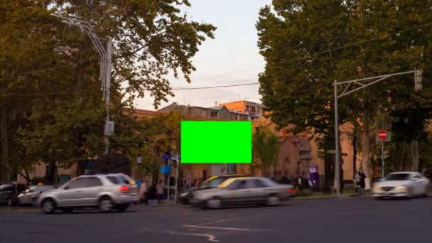 4K TIME LAPSE video. Advertising billboard with green screen in the center of the autumn cityscape with blurred walking people and cars.