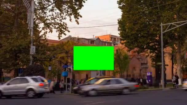 TIME LAPSE video. Advertising billboard with green screen in the center of the autumn cityscape with blurred walking people and cars. Camera moves away