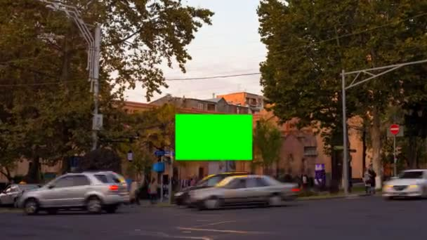 TIME LAPSE video. Advertising billboard with green screen in the center of the autumn cityscape with blurred walking people and cars. Camera is approaching
