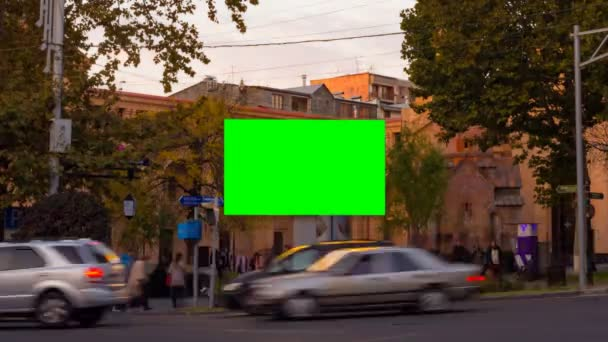TIME LAPSE video. Advertising billboard with green screen in the center of the autumn cityscape with blurred walking people and cars