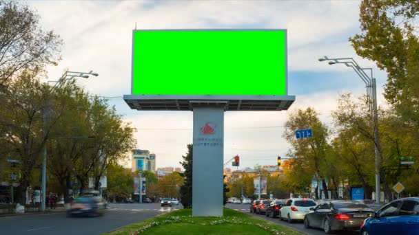 4K TIME LAPSE video. The Big Advertising billboard with green screen in the center of the autumn cityscape with traffic cars and people against the background of moving white clouds. Day becomes night
