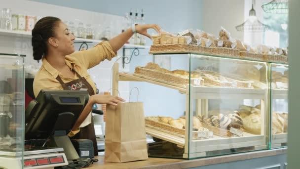 Happy africké ženské pekař pracuje v její pekárně uvedení soubory cookie do nákupní tašky pro její klient radostně usmívat na fotoaparát, nabízející prodej prodej prodejce shop assistant služby nákupu