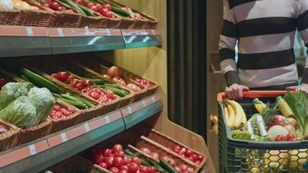 Vágott elérve a zöldségek polc, míg vásárlás a szupermarketben, élelmiszerboltok copyspace friss termék egészséges táplálkozás finom vitamin Vegán vegetáriánus étel csinál ember lövés közelről
