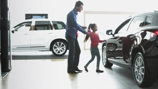 Dad with daughter are looking on the new car. The are in car dealership.