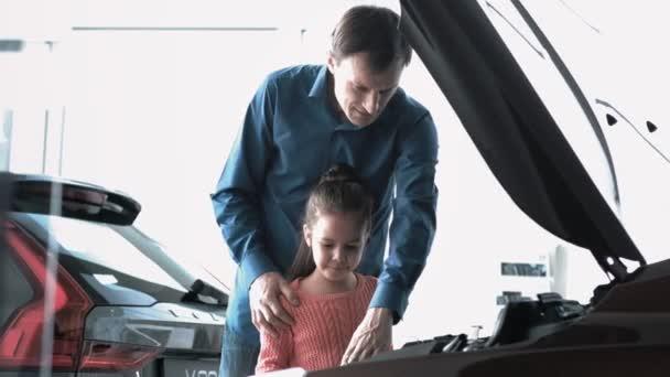 Táta se zobrazí jeho dcera auto motor. Ona se snaží dotknout co.