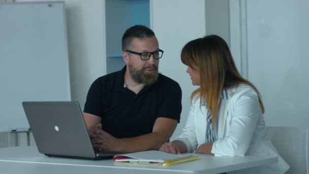 Co-workers in office. Middle-aged man with a beard and glasses sits with a colleague at the laptop in the office