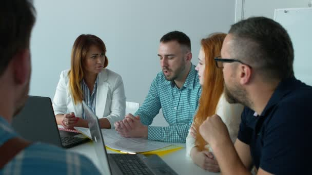 Two young guys and two beautiful girls dressed in business casual discuss business while working in the office.