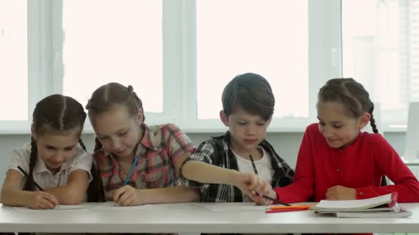 Four children draw together. Three girls and one boy try to paint together a masterpiece of world art