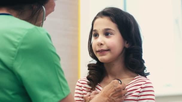 Pädiatrische Checkup. Hübsches junges Mädchen immer von ihrem Kinderarzt professionelle Kinderarzt Arzt untersuchen ihre junge Patientin mit einem Stethoskop Medizin Gesundheitswesen Kinder Beruf geprüft