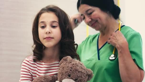 Důvěřující její lékař. Krásná mladá dívka objímá její medvídek s úsměvem během pediatrické vyšetření profesionální pediatr starší žena zkoumání svého mladého pacienta pomocí stetoskopu zdraví medik