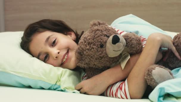 Ma túl fáradt. Aranyos boldog fiatal lány feküdt neki rossz átölelve neki mackó játék mosolyog a kamerába, alvó gyermekek gyerekek gyermekkori boldogság álmos alvás pihenés pihenés többi fogalma alá tartozó