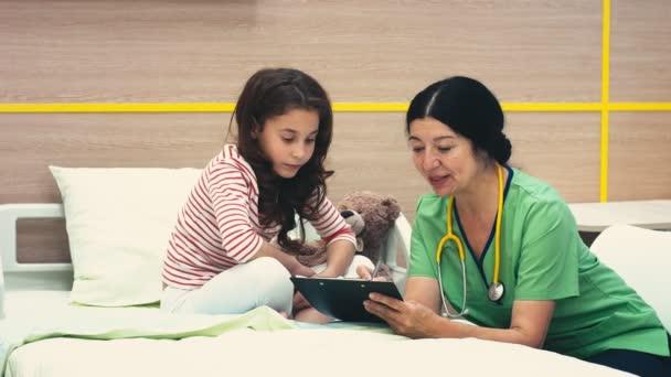 Zeige Ergebnisse. Ältere Frau professionelle Kinderarzt im Gespräch mit ihren jungen Patienten Krankenhaus Gesundheit Krankheit Krankheit Kindheit Kinder Kinder Beruf Beruf medizinische Klinik Kommunikationskonzept