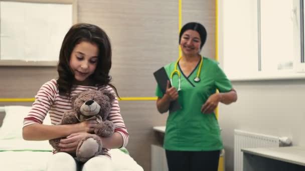 Pocit zdraví. Krásná mladá dívka s úsměvem do fotoaparátu pózuje se svým plyšovým medvědem ukazuje palec nahoru šťastně její pediatr, hrdě pózuje na pozadí copyspace lékař lékařské péče