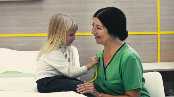 Rollenwechsel. kleines nettes blondes Mädchen spielt Arzt, hört dem Herzschlag ihres Kinderarztes mit einem Stethoskop kleines Mädchen untersucht ihren Arzt mit einem Stethoskop spielt lustiges Glück
