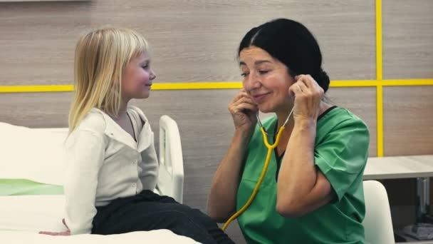freundliche doc. fröhliche Seniorin Kinderärztin mit Stethoskop untersucht ihre kleine Patientin auf der Krankenstation Kinder Kind Professionalität Gesundheit Beruf Atmung Berufskonzept