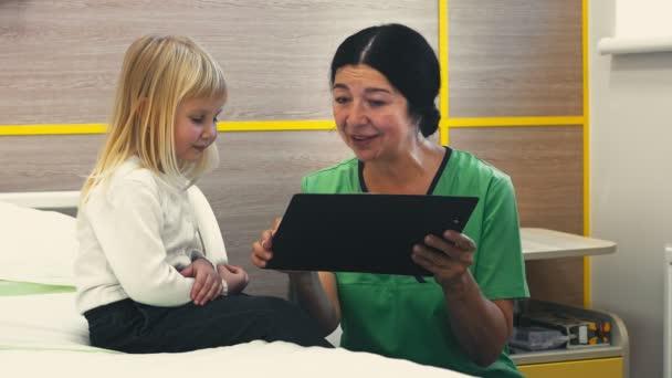 Holčičku. Rozkošná holčička s úsměvem poslouchal její pediatr, sedící na posteli na nemocnici přátelští lidé zdravotní péče nemocnice lékařské odbornosti okupace péče dětem koncept