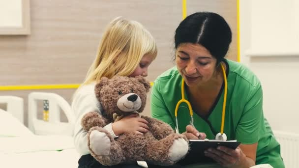 Talking to her patient. Professional pediatrician talking to her little patient showing her something on a clipboard hospital ward health sickness illness children friendly kindness profession concept