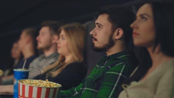 Egy fiatal srác kommunikál egy gyönyörű lány a moziban