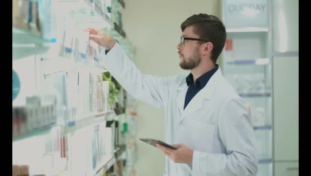 Young guy pharmacist examines drugs on the rack