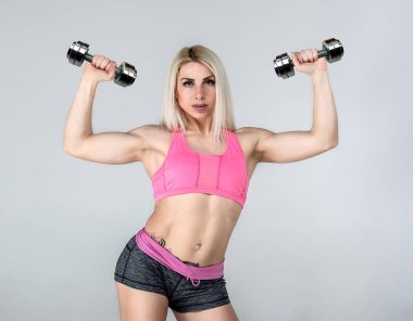 A young girl is engaged in fitness. Sports girl. Coach. bodybuilder