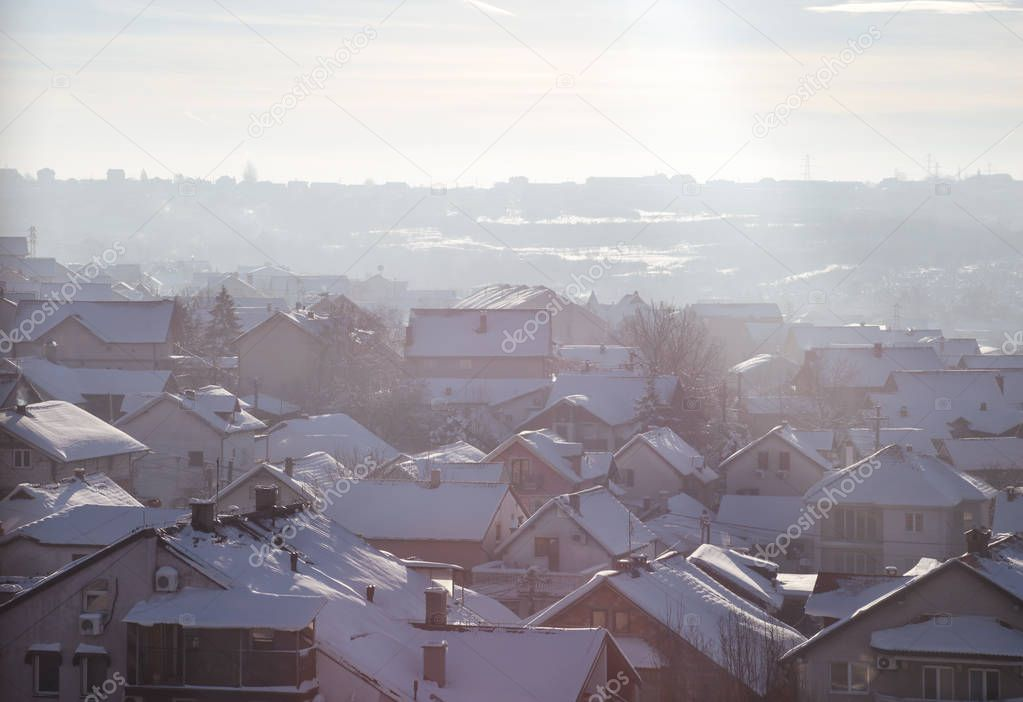 Beautiful view of winter morning fog, snow and sun filling on landscape of houses and buildings in Belgrade. Scenery during sunrise, sunset of top view at settlement is very popular for photographer.