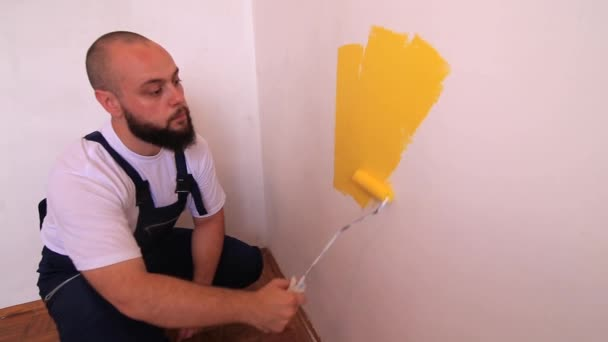 Bauarbeiter und Handwerker bei Renovierungsarbeiten in der Wohnung. professioneller Maler mit Pinselwalze Malerei der Wand mit gelber Farbe auf der Baustelle. Sanierungskonzept für Eigenheime.