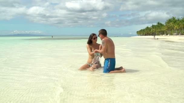 Muž a žena navzájem šplouchání vody v moři