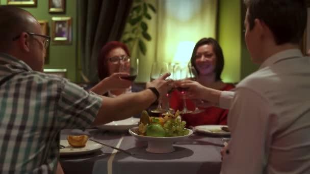 Skupina přátel sedět u stolu v restauraci přiťuknete a pít červené víno