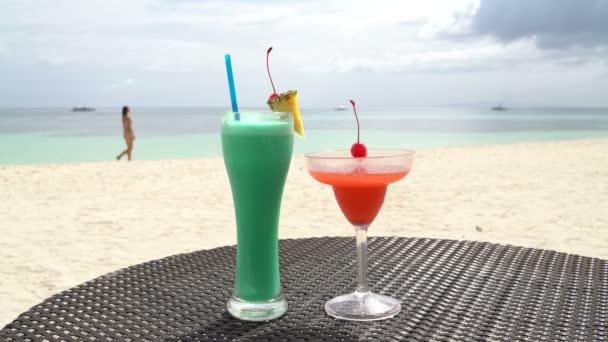 Cocktails stehen auf dem Tisch. Mädchen spaziert am Meer entlang