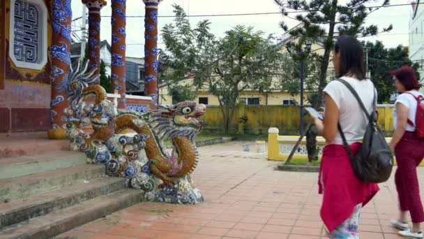 Women are photographed with a dragon statue
