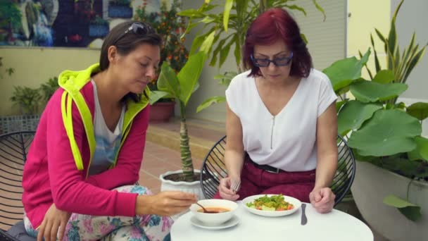 Women eat in the restaurant on the street pumpkin soup and vegetable salad with shrimps