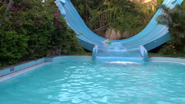 Woman riding a croissant on a water slide in the water park