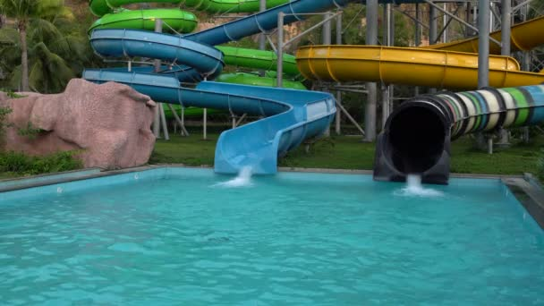 In the water park, a woman rolls on a croissant on a water slide