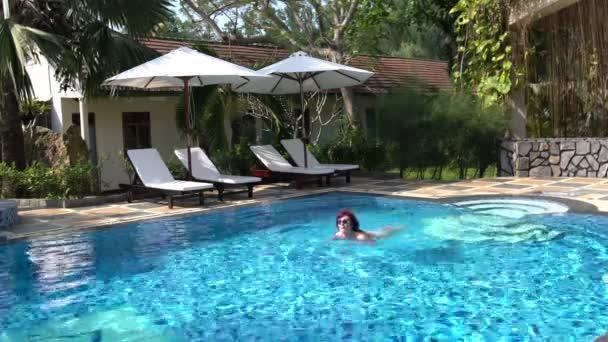 Žena plave v bazénu pod širým nebem