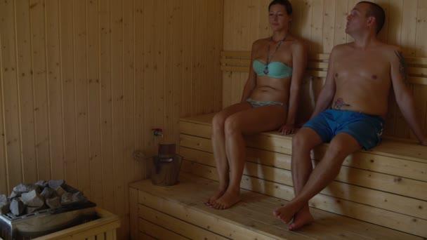 Pár, sedět v sauně v komoře a mluví