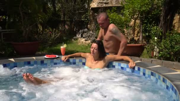 Woman relaxes in the jacuzzi. Comes man and massages the shoulders woman