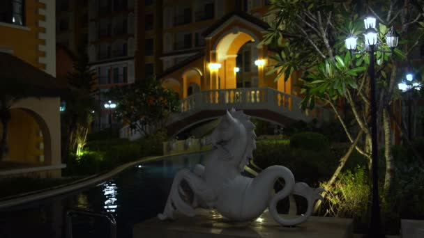 Night outdoor swimming pool with a statue of Capricorn and bridge