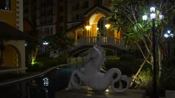A woman stands on the bridge and looks at night outdoor swimming pool with a statue of Capricorn.
