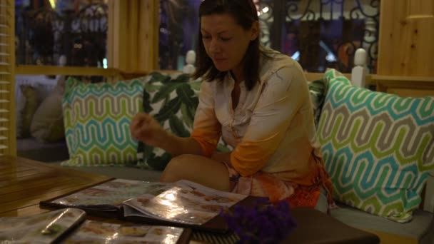 Woman sitting in a restaurant and looking menu