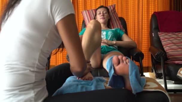 Thajská masáž. Masérka masíruje Šin Zenske. Žena uvolňuje, sedí v křesle