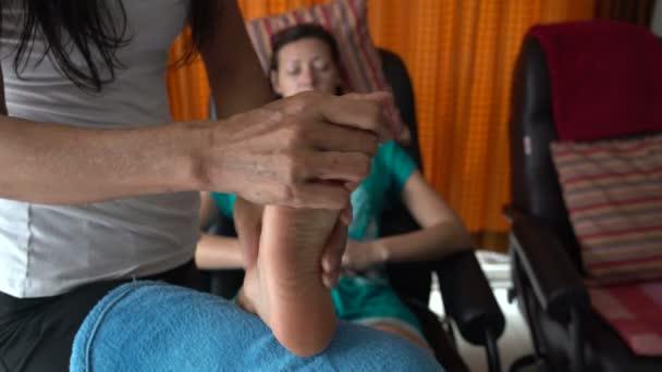 Thajská masáž. Masérka masíruje Zenske nohy. Žena uvolňuje, sedí v křesle
