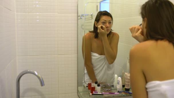 Nő egy törülközőt vonatkozik make-up, fest a szeme előtt a tükör a fürdőszobában ceruzával