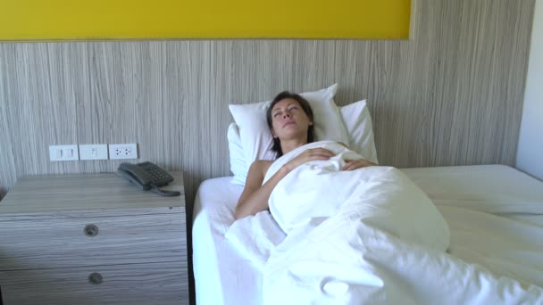 A woman calls to phone lying in bed