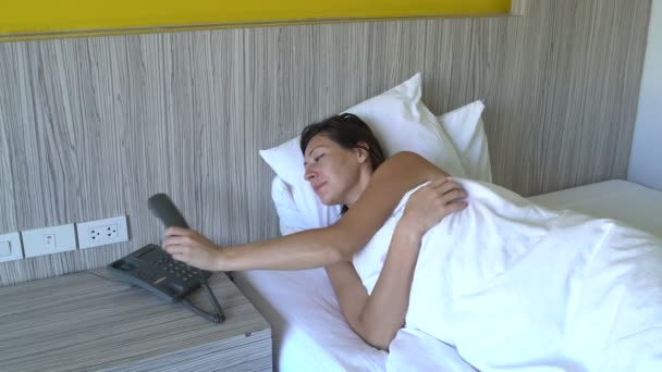 A woman wakes up in bed at the hotel and call phone.